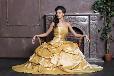 Elegant  beauty posing in a golden dress photo