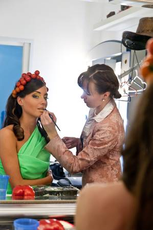 the stylist paints model in a make-up room before shooting photo