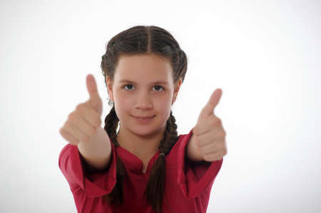 Closeup of girl showing thumbs up in both hands photo