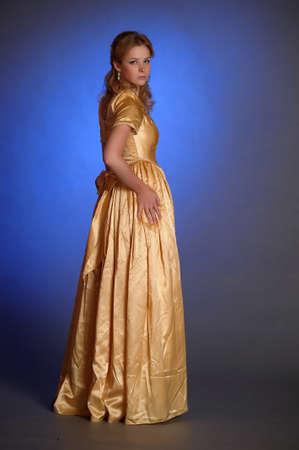 joven y bella mujer en vestido de oro photo