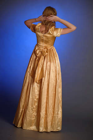 beautiful young woman in gold dress photo