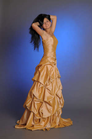Brunette in a beautiful gold dress Stock Photo - 14167643