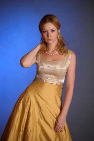 beautiful young woman in gold dress photo
