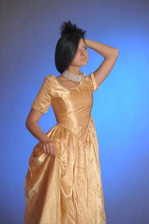 Elegant girl beauty posing in a golden dress Stock Photo - 14403227