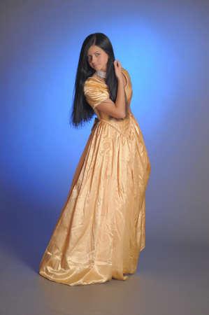 Elegant girl beauty posing in a golden dress photo