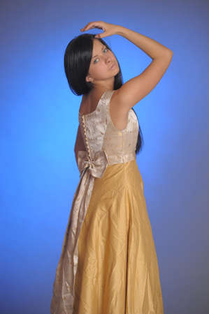 Elegant girl beauty posing in a golden dress photo