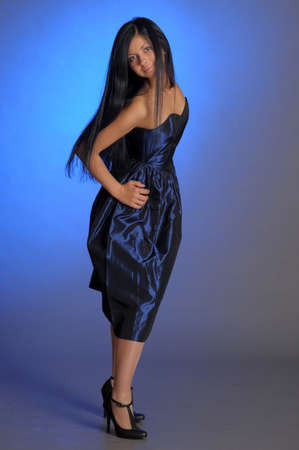 dramatic dark-haired girl in a blue dress Stock Photo