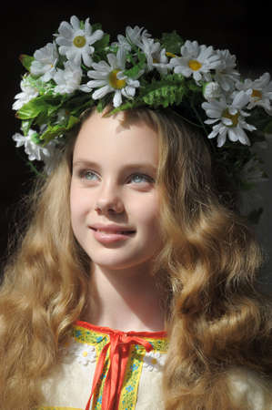blonde girl with a wreath of daisies photo