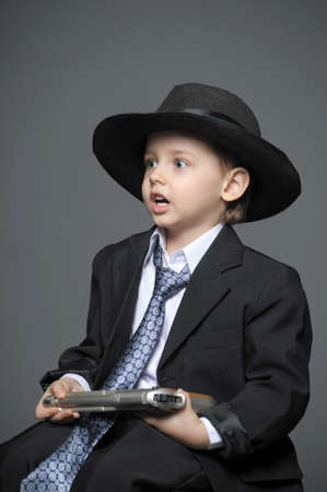 barefoot cowboy: Boy in a suit and a hat with a gun Stock Photo