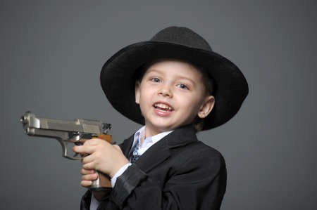 Boy in a suit and a hat with a gun photo