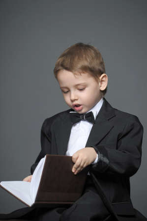 Boy in a suit with a book photo