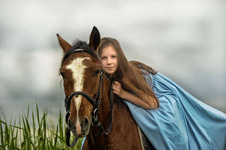 young girls nature: girl in long dress with a horse Stock Photo