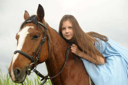 historical events: girl in long dress with a horse Stock Photo