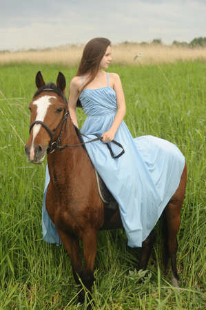 seductive expression: girl in long dress with a horse Stock Photo