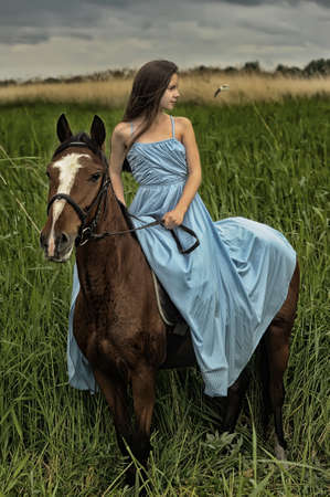 historical clothing: girl in long dress with a horse Stock Photo
