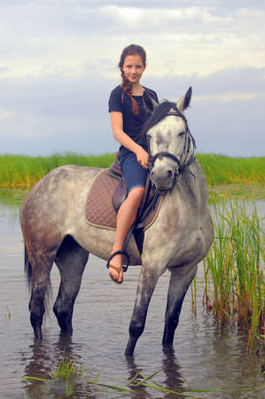 woman and horse: teen girl on a horse in the water