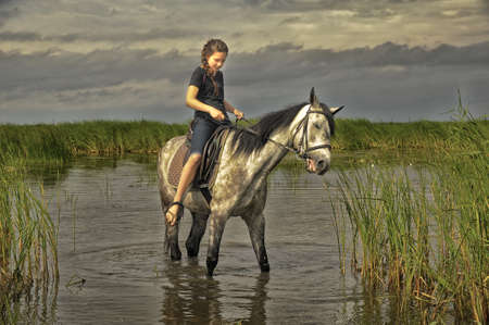 teen girl on a horse in the water