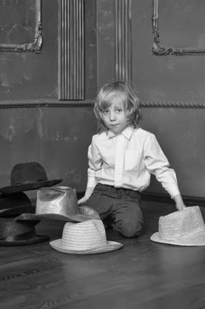 the boy measures at once many hats photo