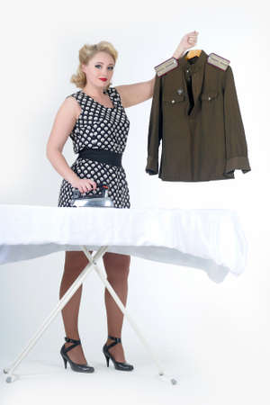 the young girl irons a soldier s blouse photo