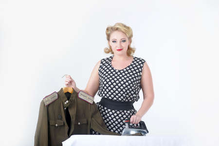 the young girl irons a soldier s blouse Stock Photo - 14167654