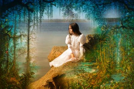 traje de gala: Hermosa chica se sienta en un acantilado al atardecer mirando el mar