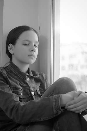 The sad girl the teenager at home on a window sill Stock Photo - 14190805