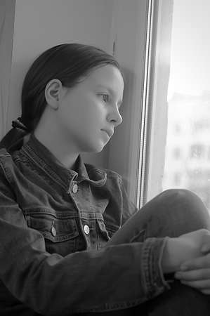 angst: The sad girl the teenager at home on a window sill