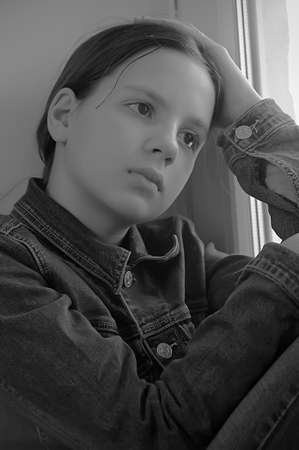The sad girl the teenager at home on a window sill Stock Photo - 14190808