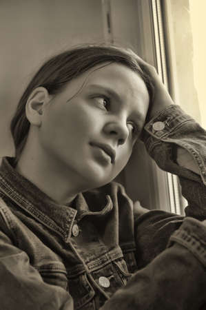 The sad girl the teenager at home on a window sill photo