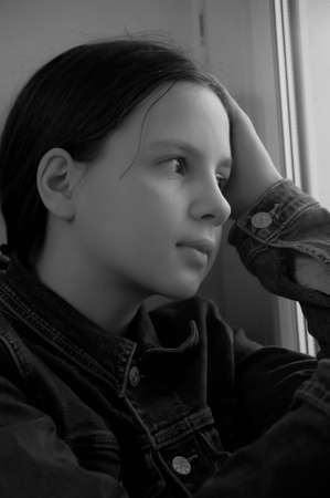 The sad girl the teenager at home on a window sill Stock Photo - 14190803