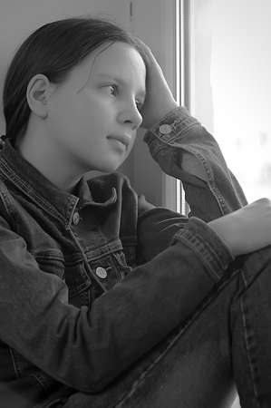 sill: The sad girl the teenager at home on a window sill