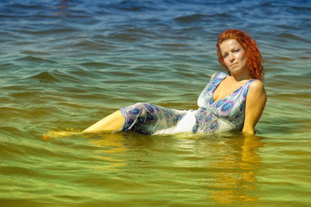 young woman in a dress in the water photo