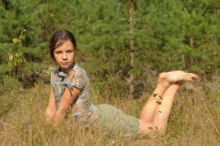 adolescence: teen girl lying in grass Stock Photo