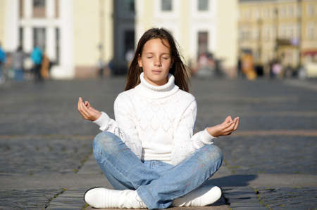 The girl meditates in the middle of street  photo