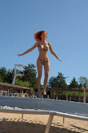 The girl jumps on a trampoline on a beach  photo