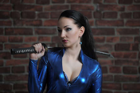 girl in a blue suit with a fitting close katana in hands Banco de Imagens