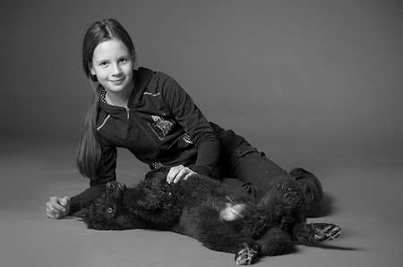 The girl the teenager with a black puppy in studio photo