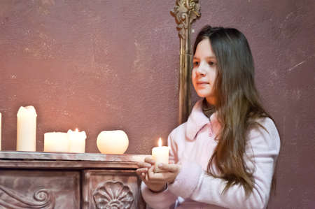 The girl the teenager at a fireplace with candles Stock Photo - 14235442
