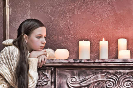 The girl the teenager at a fireplace with candles Stock Photo - 14235437