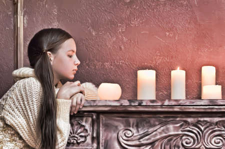 The girl the teenager at a fireplace with candles Stock Photo - 14235438