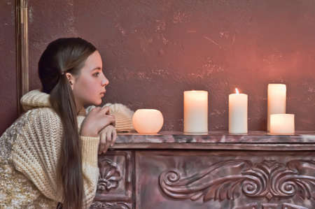 The girl the teenager at a fireplace with candles Stock Photo - 14235431