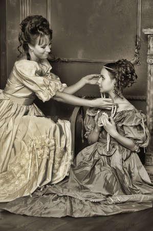 era: Two ladies in medieval dresses, sepia photos Stock Photo