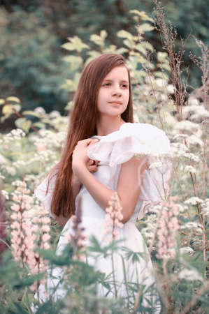 Young girl in white dress walks in field photo