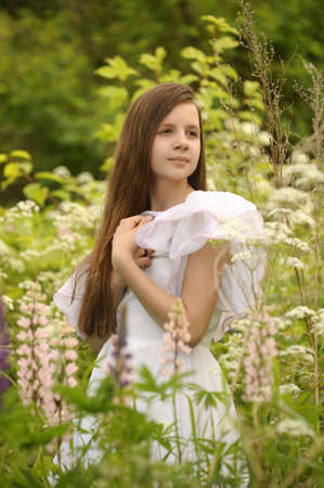 Young girl in white dress walks in field Stock Photo - 14308667