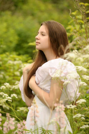 Young girl in white dress walks in field Stock Photo - 14308666