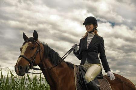 riding helmet: Mujer que monta un caballo Foto de archivo