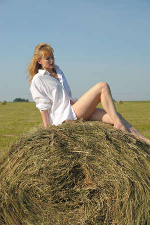 Young woman and huge haystack photo