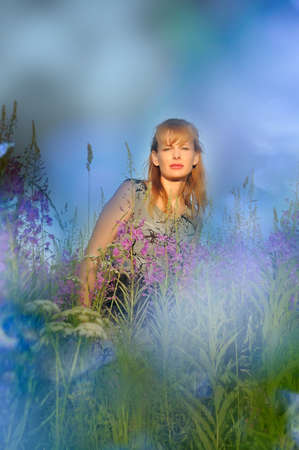 The beautiful young woman in the field of violet flowers  photo
