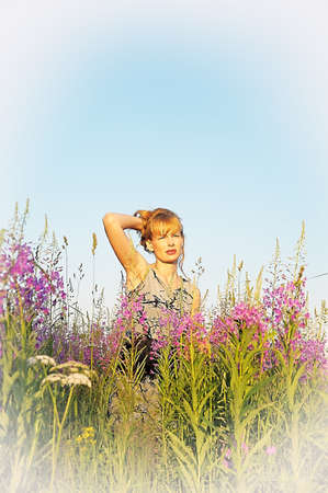 The beautiful young woman in the field of violet flowers