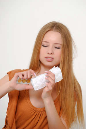 Woman bite the pack of medicine aspirin tablets photo